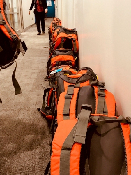 Photo: Assembled backpacks lined up, waiting to be packed into boxes